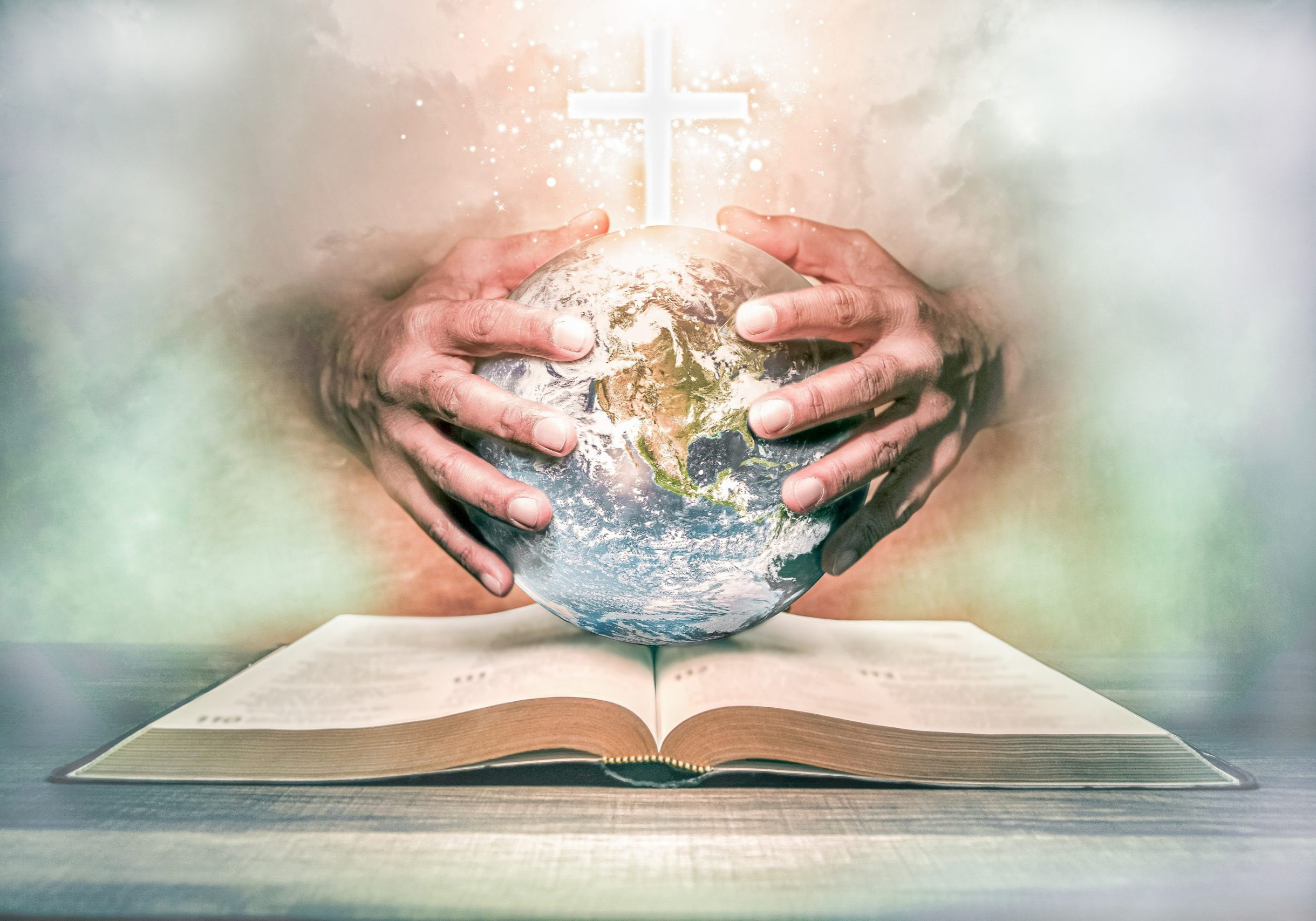 Hands holding the world on a open bible.